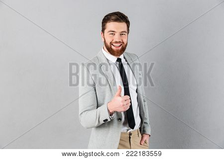 Portrait of a cheerful businessman dressed in suit showing thumbs up and looking at camera isolated over gray background