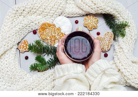 Hands In A Sweater Holding A Cup Of Tea And A Cookie On A Wooden Table.