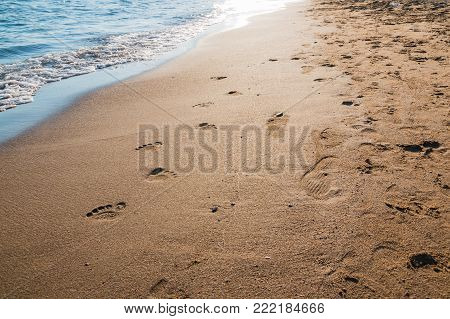 Footprints in wet sand of beach and wave