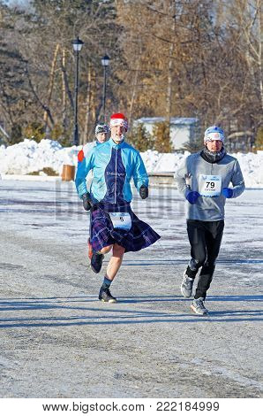Editorial. Omsk, Russia - January, 07 2018. Runners of different nationalities and ages running along the Embankment of Tukhachevsky