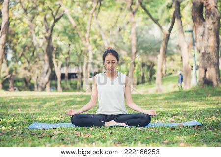 Young asian woman yoga outdoors keep calm and meditates while practicing yoga to explore the inner peace. Yoga and meditation have good benefits for health. Yoga Sport and Healthy lifestyle concept.