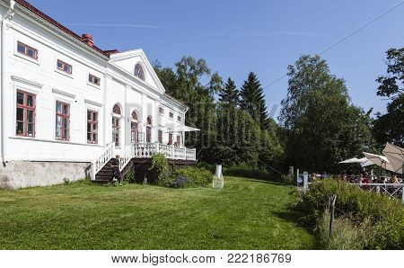 UMEA, SWEDEN ON JULY 26. View of the Baggbole mansion in bright sunshine on July 26, 2017 in Baggbole, Umea, Sweden. Café and outdoor restaurant on the balcony. Editorial use.