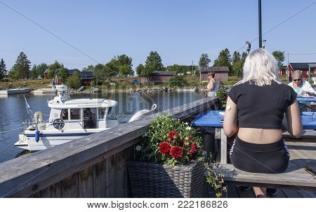 UMEA, SWEDEN ON JULY 27. View of a bridge, balcony close to the sea on July 27, 2017 in Rovagen, Sweden. Unidentified guests by the tables, marina to the left. Editorial use.