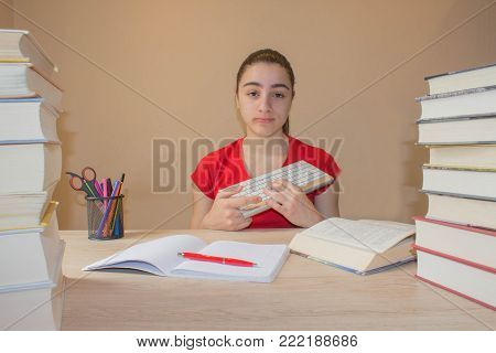 Hardback colorful books on wooden table. Young girl sitting at desk at home, doing homework. education concept
