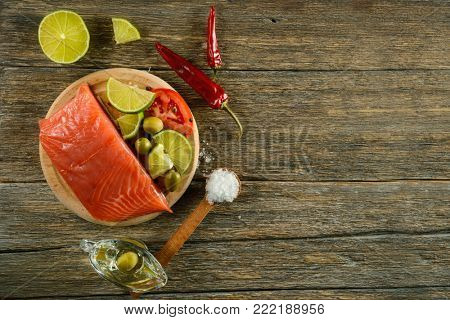 Meat red salmon fish, tomatoes, spices, lemon, green olives and olive oil on kitchen table background. Copy space. Top view