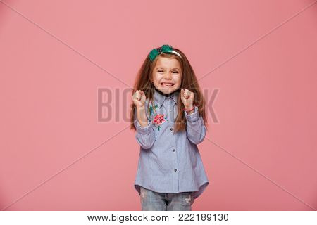 Smiling girl model in hair hoop and fashion clothes expressing happiness, gesturing with clenched fists against pink background