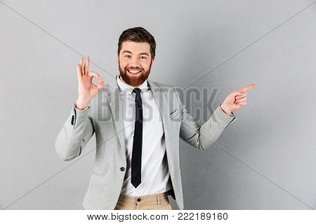 Portrait of an excited businessman dressed in suit pointing finger away and showing ok gesture isolated over gray background