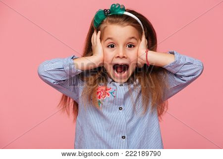 Surprised little girl covering her ears with both hands not listening or overhearing, screaming with open mouth over pink background