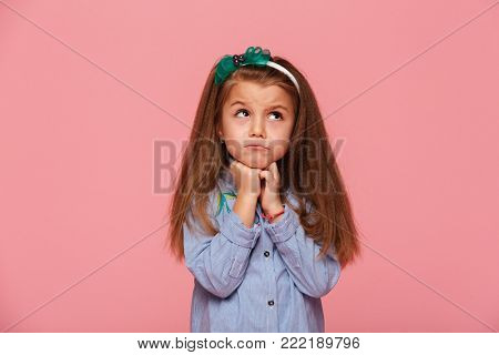 Close up photo of adorable schoolgirl 5-6 years propping up her head with fists, being upset or dreaming isolated over pink background