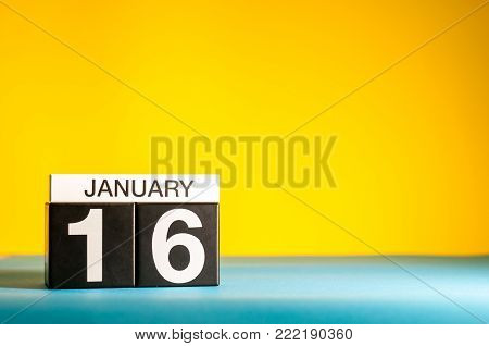January 16th. Day 16 of january month, calendar on yellow background. Winter time. Empty space for text.