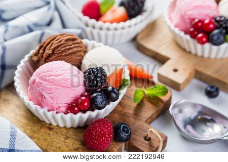 Selection of colorful ice cream scoops in white bowls, copy space