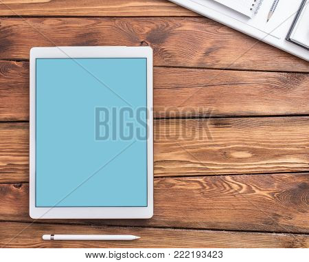 Large screen tablet device on a wooden desktop, top view. Clipping path for display.
