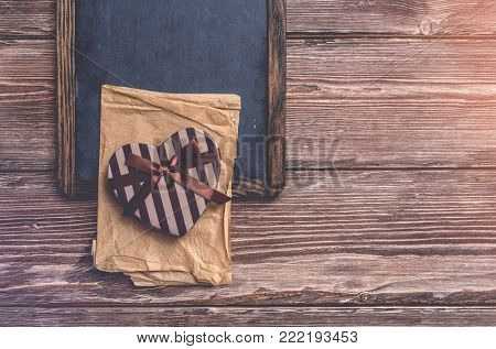 Heart shaped Valentines Day gift box over chalkboard on old wood. Top view.