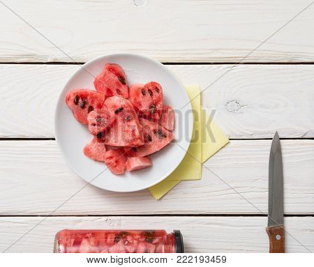 Top view of watermelon slices in shape of a heart over white wooden desk.