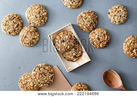 Oats cookies on a gray table in rustic style. seeds, baking in a box with a wooden spoon. Top view.