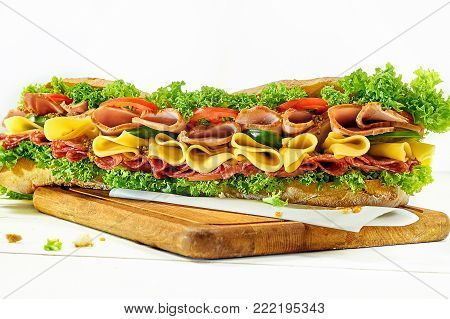 Tasty hamburger, beef burger in close-up on a plate on white wooden background.