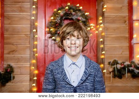 Happy child boy stands on the porch of a house decorated for Christmas. Time for miracles.