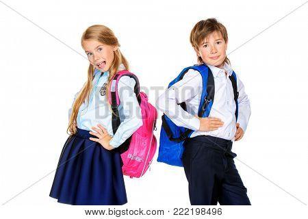 School fashion. Two cute children in school uniform and with school backpacks posing at studio. Isolated over white background. Copy space.
