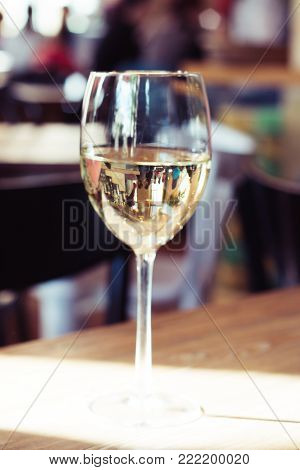 White wine in a glass in hand, rustic background, selective focus. Shadows on the wall