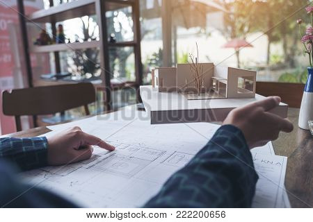 An architect working on architecture model and pointing at shop drawing paper on table