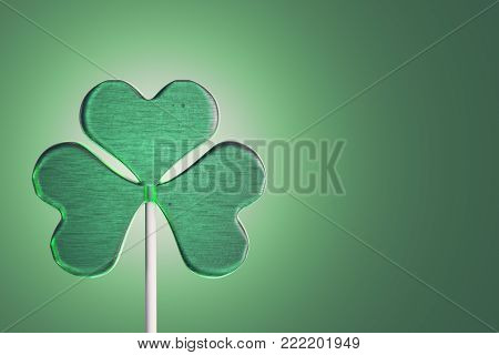 Lollipop candy in four leaf clover shape on green background with copy space. 3d rendering