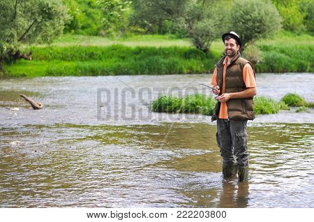 Man casts a hook on the river. Man fishing on wild river