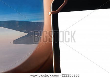 Tablet with empty space on bsckground a porthole with a view of the sunny sky and the wing of the plane.