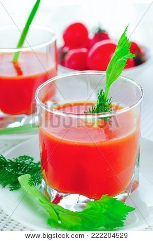 Tomato juice in a glass beaker with a branch celery and dill. Light background, soft daylight.