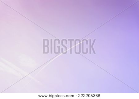 Bright clear blue sky with diagonal jet plane trace, track, Airplane trace, condensation trails, vapor trails toned in fashionable ultraviolet color of the 2018 year, purple, violet trendy background. For design, space for text