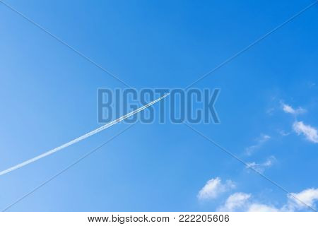 Bright clear blue sky background with diagonal jet plane trace, track, Airplane trace, condensation trails, vapor trails. With copy space