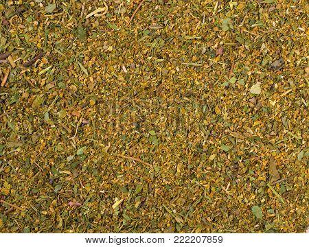 Texture background. Green spice mix khmeli suneli. Spices consist Spices consist coriander dill basil parsley celery mint laurel pepper thyme
