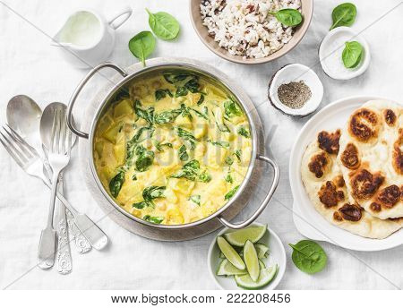 Vegetarian chickpea, spinach, potato curry pan and naan flatbread on white background, top view. Indian healthy food concept