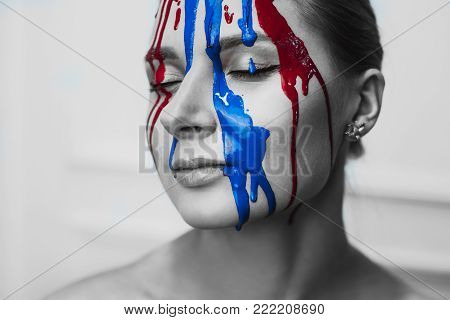 Paint on the female face, close-up. Flows of red and blue paint on the face. Artistic portrait of a hard face in paint. Black and white photos face in paint.