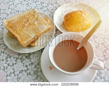 Brake time menu serve with hot coffee, toast topped with sweetened condensed milk. And bread stuffed with sausage.