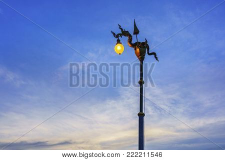 Street light or street lamp of Naga statue with white clouds and blue sky in evening , Nong Khai , Thailand