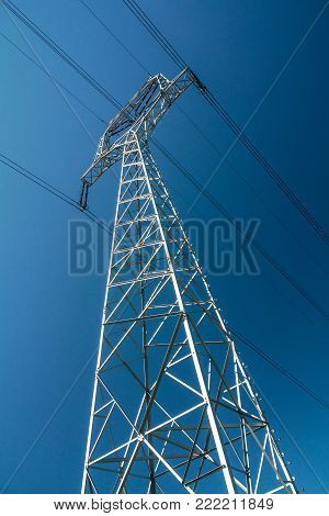 High voltage power line mast on blue sky background.