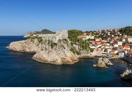 View of Fort Lovrijenac (St. Lawrence Fortress) on a steep cliff and old residential buildings by the bay in Dubrovnik, Croatia, on a sunny day.
