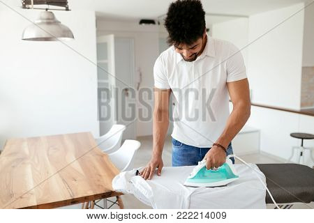Man ironing shirt on ironing board with steaming blue iron