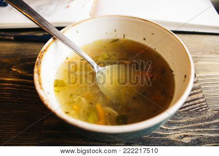 bowl of vegetable soup with parsley and beans over wooden background - healthy winter vegetarian food
