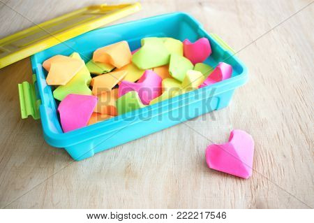 A lot of paper colorful origami heart in blue launch box and one pink heart. Origami paper hearts geometric volume. Colored paper hearts. Selective focus
