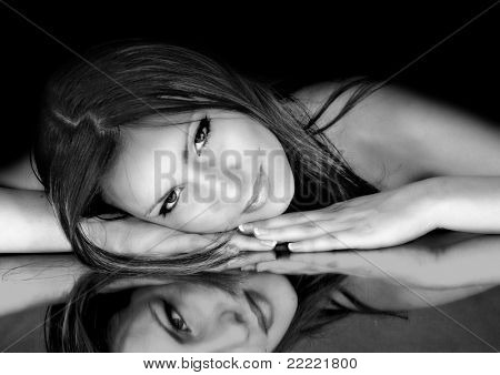 alluring woman is lying on a mirror