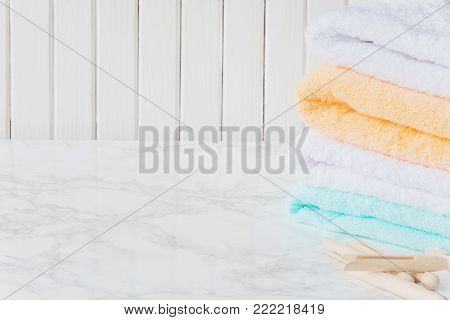 Stack of multicolored fluffy cotton bath towels and wooden clothespins are on the background of marble surface, with copy-space