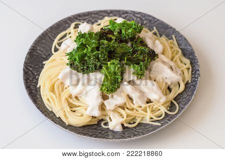 Spaghetti with sliced chicken breast in white creamy sauce and crispy kale leaves. Balanced meal