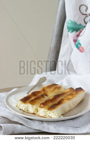 Vertuta or placinta with cottage cheese and cheese, served with sour cream. Traditional Moldovan, Romanian or Balkan pie or cake. Rustic style, selective focus.