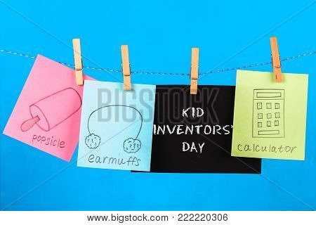 Notes hang on clothes pegs with drawings of children's inventions - popsikl, Earmuffs, calculator on a blue background. Text - Kid Inventors' Day