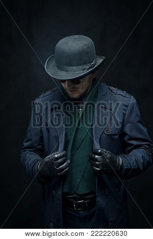 The killer in gloves puts on a raincoat on a black background