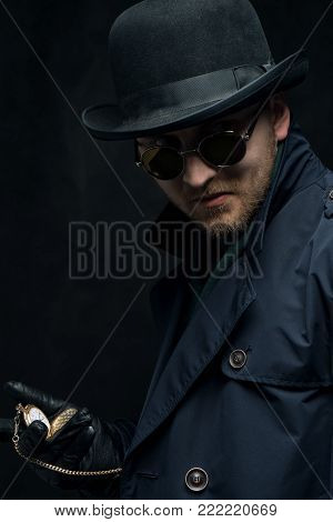 Robbery. The robber wearing  gloves is holding a gold watch in his hands.