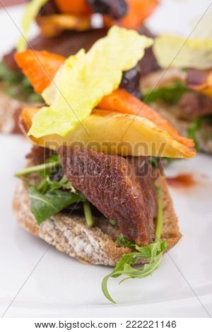 Roasted beef cheek on a toast served with sauted carrot.