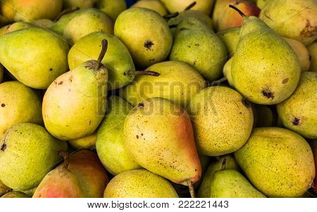 many fresh green pears in a wooden box on market at daytime
