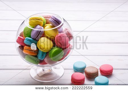 Macaroons in a glass vase on a white wooden background. Sweet macaroons. copy space. Party sweets. Happy luxury birthday and wedding concept.